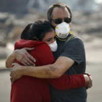 """Howard Lasker, right, comforts his daughter, Gabrielle, who is visiting their home for the first time since a wildfire swept through it, Sunday, Oct. 15, 2017, in Santa Rosa, Calif. With the winds dying down, fire officials said Sunday they have apparently """"turned a corner"""" against the wildfires that have devastated California wine country and other parts of the state over the past week, and thousands of people got the all-clear to return home. (AP Photo/Jae C. Hong)"""