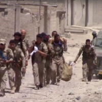 """This frame grab from video released on July 04, 2017 and provided by Furat FM Activist-Run, shows U.S.-backed Syrian Democratic Forces (SDF) fighters in the eastern side of the city of Raqqa, Syria. On Tuesday, the US military said the wall was breached after targeted airstrikes, allowing the fighters """"to advance into the most heavily fortified portion"""" of the city. (Furat FM Activist-Run, via AP)"""