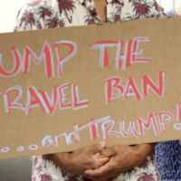 Critics of President Donald Trump's travel ban hold signs during a news conference with Hawaii Attorney General Douglas Chin, Friday, June 30, 2017 in Honolulu. Chin says the scaled-back version of Trump's travel ban has illogical standards for who should be prohibited from entering the country. Chin questioned why a stepbrother or stepsister should be allowed into the country but not a grandmother. The Trump administration set new criteria Thursday barring some citizens from six majority-Muslim countering from coming to the United States. (AP Photo/Caleb Jones)