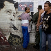 People search for their names on voter lists for mayoral elections by a mural of Venezuela's late President Hugo Chavez at a school serving as a polling station in Caracas, Venezuela, Sunday, Dec.10, 2017. Venezuelans will choose hundreds of mayors on Sunday in elections pitting candidates backed by President Nicolas Maduro against a fractured opposition still bruised by a poor showing in recent gubernatorial voting. (AP Photo/Ariana Cubillos)